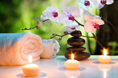 Massage composition spa with candles, orchids and black stones in garden. 