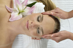 Massage at the day spa. Young woman lying on massage table at spa, eyes closed Royalty Free Stock Images