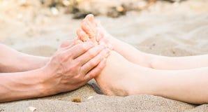 Massage de pied dans le sable, le mâle et le Caucasien féminin Photo libre de droits