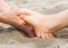 Massage de pied dans le sable, le mâle et le Caucasien féminin Image stock