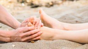 Massage de pied dans le sable, le mâle et le Caucasien féminin Photos libres de droits