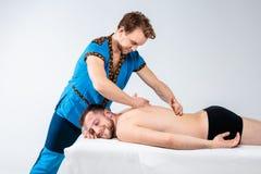 Massage de thème et soin de corps Le bel homme caucasien dans l'uniforme bleu et la barbe faisant l'étirage, guérit, diagnostic d image libre de droits