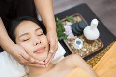 Massage de visage Plan rapproché de jeune femme atteignant le traitement de massage de station thermale le salon de station therm photographie stock