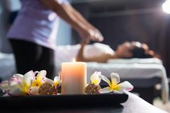 Massage decoration with blur Thai massaging. Candle and plumeria flower for massage decoration with blurred Asian woman having Thai oil massaging in spa resort royalty free stock photography