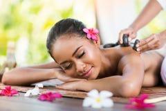 Massage der Rückseite mit Steinmassage stockfotografie