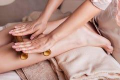 Massage des menschlichen Fußes im Badekurortsalon mit Bambusstöcken Stockfotos