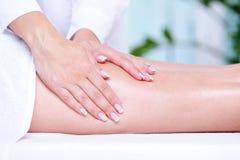 Massage des weiblichen Fahrwerkbeines Stockfoto