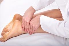 Massage des weiblichen Fahrwerkbeines. Lizenzfreie Stockfotografie