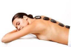 Massage en pierre. Belle femme obtenant à station thermale le massage chaud de pierres Photo libre de droits
