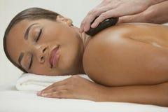 Massage en pierre chaud de demande de règlement de station thermale de santé de femme Photos libres de droits