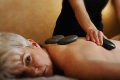 Massage en pierre chaud de station thermale aînée de santé Photo libre de droits