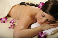 Massage en pierre minéral chaud et fleurs de station thermale Images libres de droits