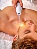 Massage för häleri för ung man elektrisk ansikts- arkivbild
