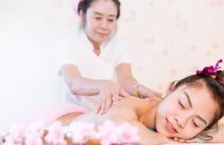 Massage för kvinnahäleriolja på baksidan i thailändsk massagebrunnsort Arkivbilder