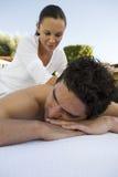 Massage för manhäleribaksida av en massör Arkivbild