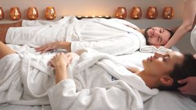 Massage för två par i brunnsortsalongen Dubbletthuvudmassage för vänner arkivfilmer