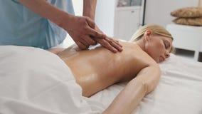 Massage für attraktive blonde junge Frau im Badekurortraum Stockbilder