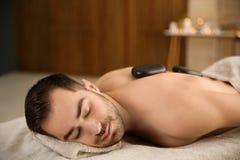 Massage f?r sten f?r stiligt manh?leri varm i brunnsortsalong royaltyfri fotografi
