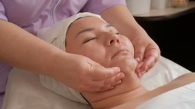 Massage facial anti-vieillissement Les mains d'un cosmetologist professionnel lisse la peau sur le visage d'une fille asiatique S banque de vidéos