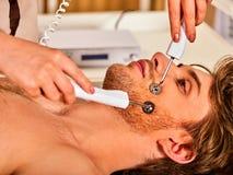 Massage facial au salon de beauté Soins de la peau électriques de femme de stimulation Images stock