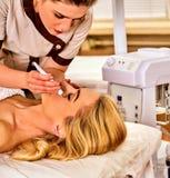 Massage facial au salon de beauté Soins de la peau électriques de femme de stimulation Image stock