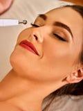 Massage facial au salon de beauté Soins de la peau électriques de femme de stimulation Image libre de droits