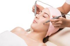 Massage facial, brune paisible obtenant le dermabrasion micro du thérapeute de beauté images stock