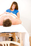 Massage: Focus on Man's Head on Massage Table. Series of a young couple getting massages by therapists.  Together, as well as separate.  Bright and clean Stock Photo