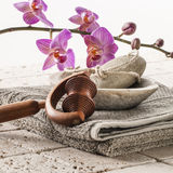 Massage and footacre with femininity. Spa and wellbeing concept - pumice stone,massage roll and cotton towel with pink orchid flowers for washing-up tools and Royalty Free Stock Image