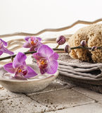 Massage and footcare with femininity. Spa and wellbeing concept - pumice stone,natural sponge and cotton towel with pink orchid flowers for washing-up tools and Stock Photos