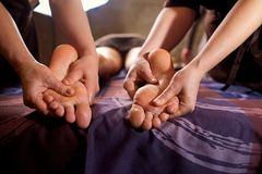 Massage in four hands on feet in the spa salon. Two massage therapist make massage for a woman Stock Photography