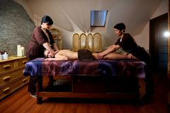 Massage in four hands in the spa salon. Two massage therapist make massage for a woman Royalty Free Stock Image