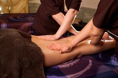 Massage in four hands in the spa salon. Two massage therapist make massage for a woman Stock Images