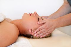 Massage of the head and face in spa center Stock Photos