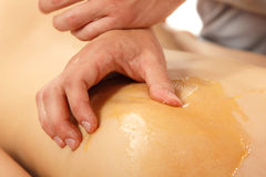 Massage with honey on back of woman young Royalty Free Stock Photography