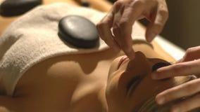 Massage with hot basalt stones. Beautiful deep charming light stock video footage