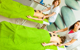 Massage with hot rocks stones in beautician Stock Photo