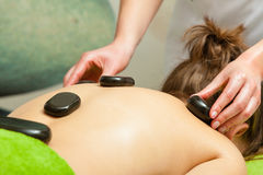 Massage with hot rocks stones in beautician Stock Image