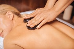 Nice skilled masseuse using hot stones for massage. Massage with hot stones. Nice skilled masseuse using hit stones while doing a massage for her client royalty free stock photo