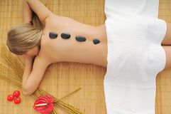 Massage with hot volcanic stones royalty free stock images