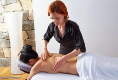 Massage i kvinnabaksida med fysioterapeuten Royaltyfria Bilder