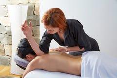 Massage i kvinnabaksida med fysioterapeuten Arkivbilder