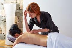 Massage i kvinnabaksida med fysioterapeuten Royaltyfri Foto