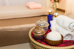 Massage item and Spa Oil in Basket on Bed Stock Photo