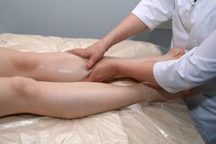 Massage of legs. The masseur makes massage of legs in a massage-room royalty free stock image