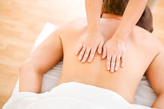 Massage: Man Gets Throrough Back Massage. Series of a young couple getting massages by therapists.  Together, as well as separate.  Bright and clean Royalty Free Stock Image
