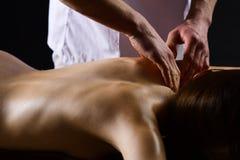 massage massagem dos termas e tratamento do corpo o homem faz a massagem para a mulher despida massagem do corpo no salão de bele fotografia de stock