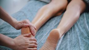 Massage - massage master massaging womans legs and feet with oil