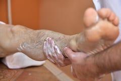 Massage med vulkaniska stenar och händer Arkivfoto