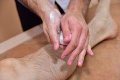 Massage med vulkaniska stenar och händer Royaltyfri Bild